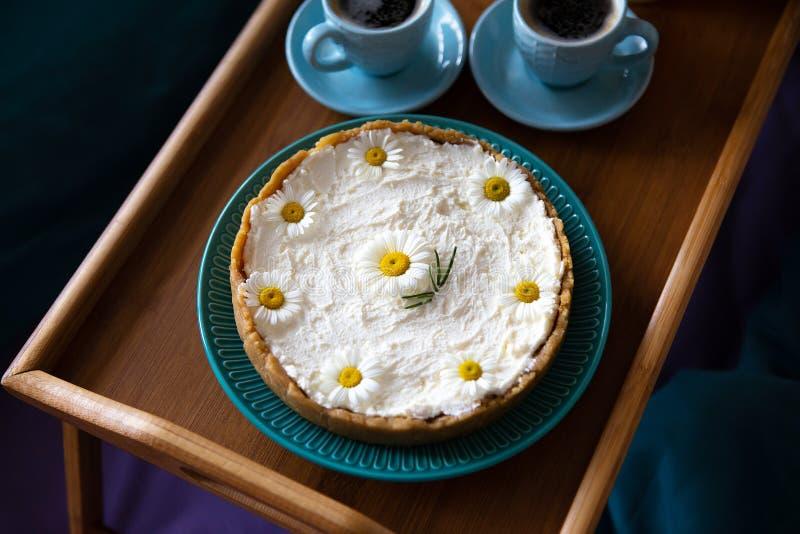 Взгляд сверху - завтрак в кровати очень вкусный чизкейк и 2 чашки кофе на деревянном подносе стоковое фото