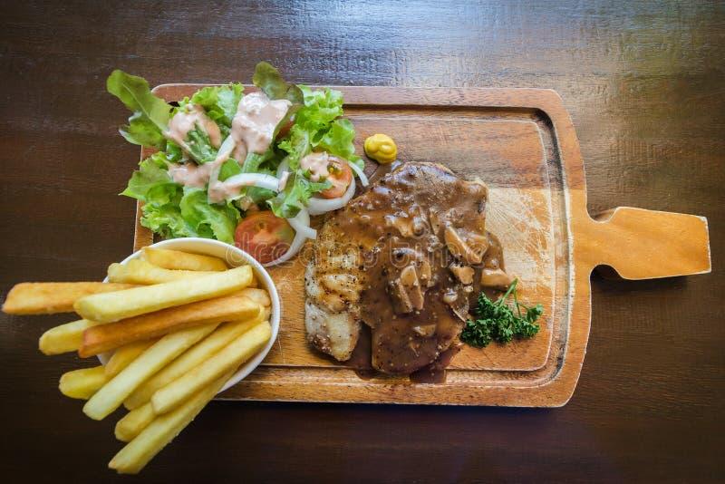 Взгляд сверху зажарил стейк с французским картофелем фри, салат свинины на деревянной плите стоковая фотография