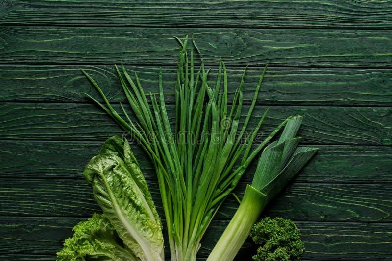 взгляд сверху зеленого лука, лук-порея и петрушки на деревянном столе, здоровом стоковое фото