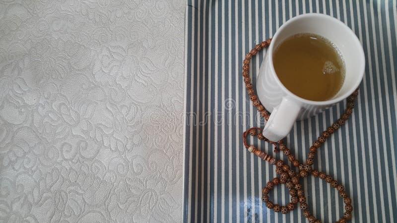 Взгляд сверху зеленого чая в чашке с шариками молитве или розарием установил в подносе стоковая фотография