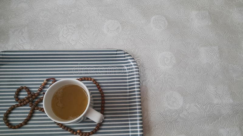 Взгляд сверху зеленого чая в чашке с шариками молитве или розарием установил в подносе стоковое фото rf