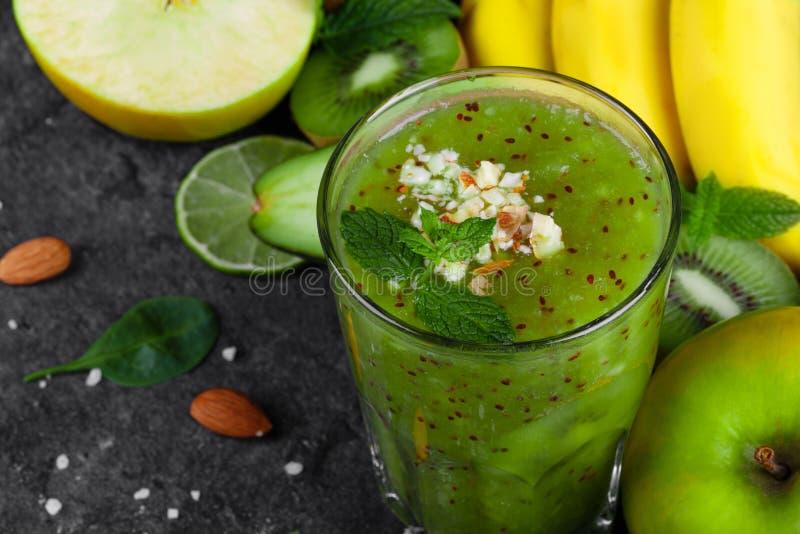 Взгляд сверху зеленого smoothie с кивиом и заскрежетанными миндалинами на темноте - серой предпосылкой Тропические плодоовощи на  стоковая фотография