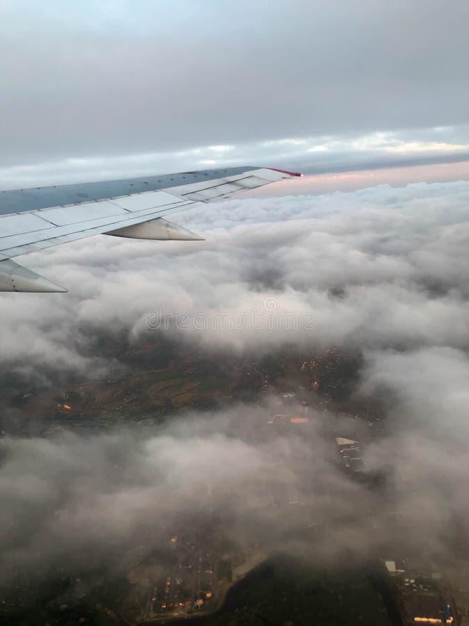 Взгляд сверху земли от иллюминатора, окон воздушных судн на крыле с двигателями, турбин и белого пушистого, clo дождя стоковые изображения