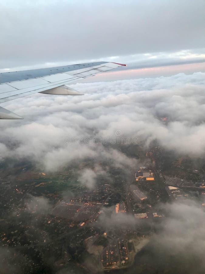 Взгляд сверху земли от иллюминатора, окон воздушных судн на крыле с двигателями, турбин и белого пушистого, clo дождя стоковое изображение