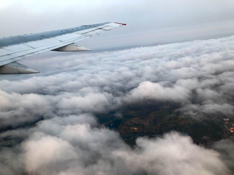 Взгляд сверху земли от иллюминатора, окон воздушных судн на крыле с двигателями, турбин и белого пушистого, clo дождя стоковое фото rf
