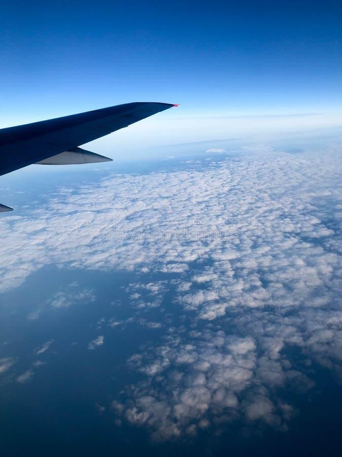 Взгляд сверху земли от иллюминатора, окон воздушных судн на крыле с двигателями, турбин и голубого моря, ocea стоковая фотография rf