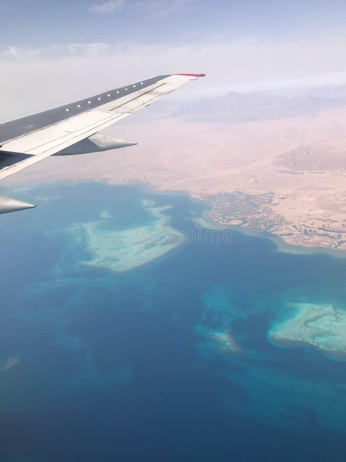 Взгляд сверху земли от иллюминатора, окон воздушных судн на крыле с двигателями, турбин и голубого моря, ocea стоковые изображения