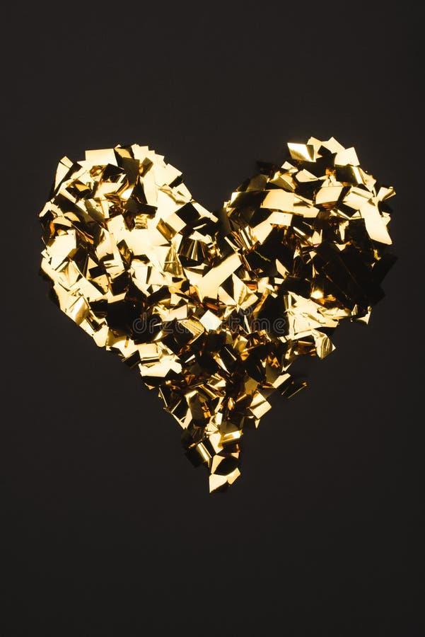 взгляд сверху золотого confetti аранжировало в форме сердца стоковое фото rf