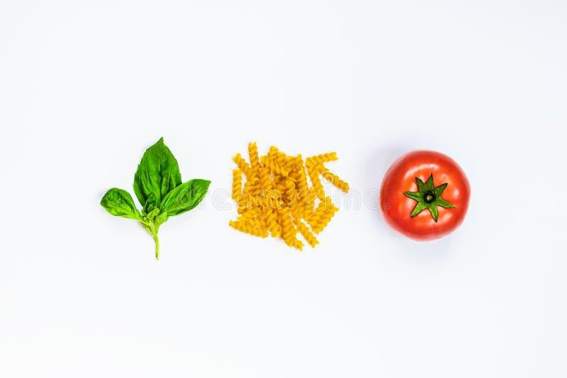 Взгляд сверху ингридиентов макаронных изделий над белой предпосылкой - сырцовым fusilli, свежим базиликом и зрелым tomatoe Италья стоковое изображение