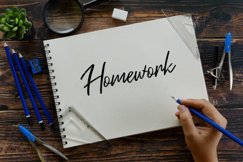 Взгляд сверху карандаша удерживания лупы, завода, ластика, канцелярских принадлежностей и руки писать домашнюю работу на тетради стоковое фото rf