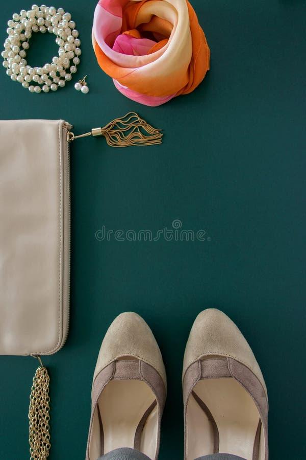 Взгляд сверху квартиры моды женской кладет на зеленую предпосылку стоковые фото