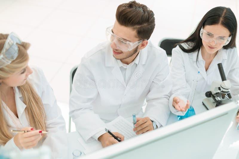 Взгляд сверху когорта ученых работая на компьютере в лаборатории стоковая фотография rf
