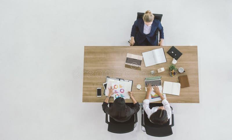 Взгляд сверху коммерсантки обсуждая работая на таблице в офисе стоковые фото