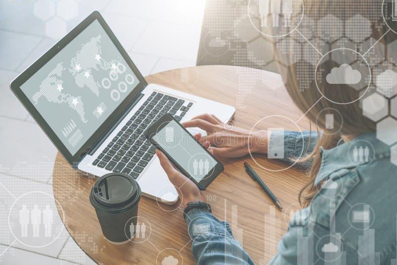 Взгляд сверху, конец-вверх smartphone пустого экрана в руках молодой женщины сидя на круглом деревянном столе и учить онлайн стоковое изображение rf