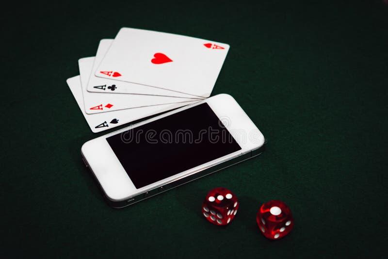 Взгляд сверху конца-вверх смартфона, dices и чешет на зеленой таблице Наркомания карт стоковое фото rf