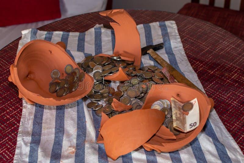 Взгляд сверху копилки в форме сломленной коричневой свиньи на таблице с много монеток и банкнотой стоковая фотография