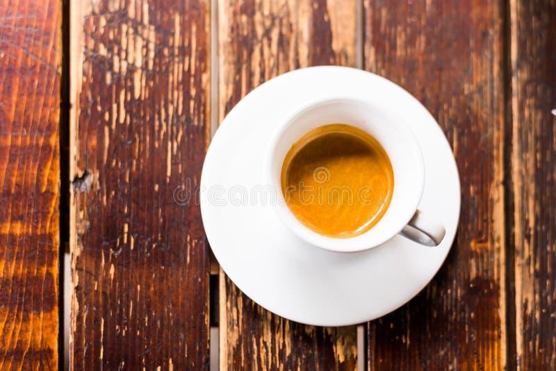 Взгляд сверху кофейной чашки на предпосылке деревянного стола стоковые изображения