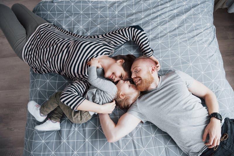 Взгляд сверху красивой молодой матери, отца и их дочери смотря камеру и усмехаясь пока лежащ на голове кровати к стоковая фотография rf