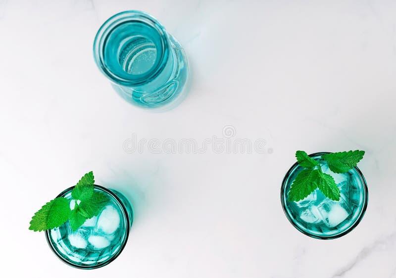 Взгляд сверху 2 красивых винтажных стекел бирюзы и бутылки с кубами холодного напитка и льда, украсил со свежим стоковые изображения