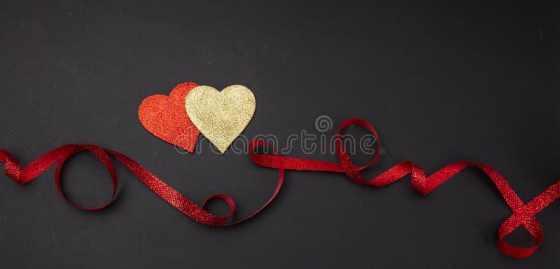 Взгляд сверху красных и золотых сердец с лентой, черной изолированной предпосылкой, знаменем стоковые изображения