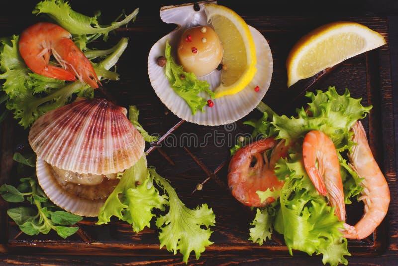Взгляд сверху креветок и scallops в раковинах с лимоном и травами на темной доске перед варить стоковая фотография