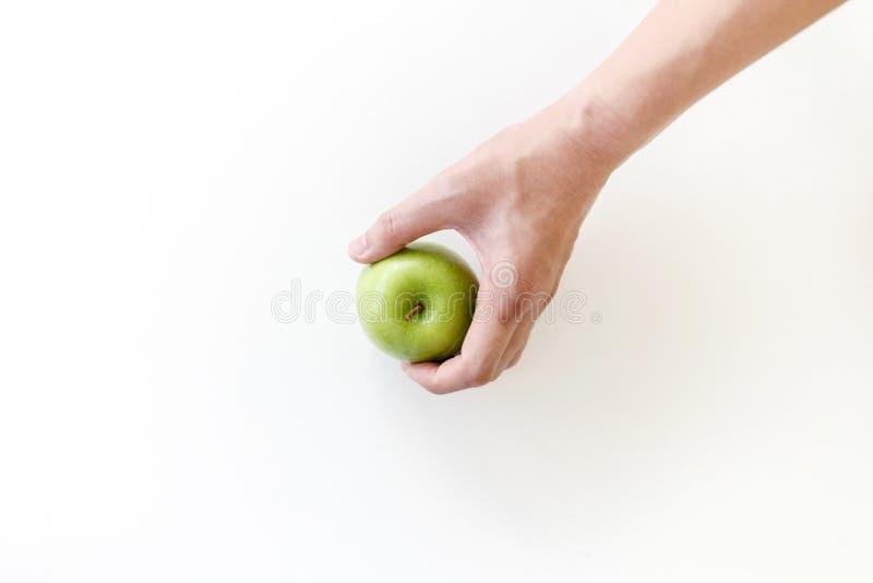 Взгляд сверху левого самосхвата руки зеленое яблоко на белой предпосылке стоковые изображения rf