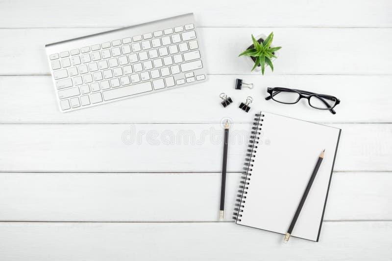 Взгляд сверху минимального стола офиса с деталями открытой пустой тетради и канцелярских принадлежностей стоковые фото