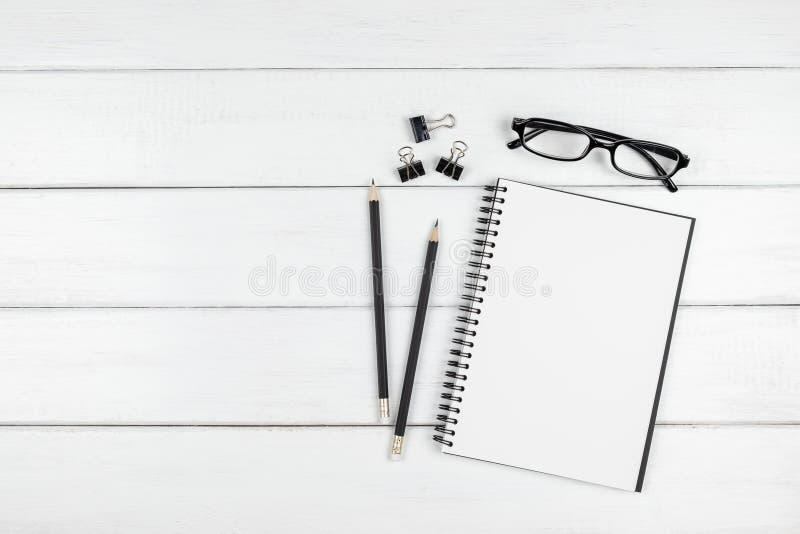 Взгляд сверху минимального стола офиса с деталями открытой пустой тетради и канцелярских принадлежностей стоковое фото