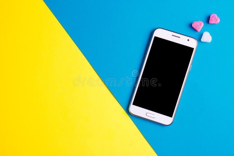 Взгляд сверху мобильного мобильного телефона и розового сердца на предпосылке бумаги искусства, космосе экземпляра Шаблон модель- стоковая фотография rf