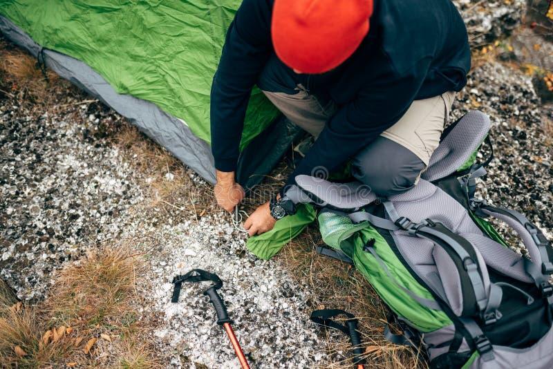 Взгляд сверху мужчины путешественника бородатого подготавливая его рюкзак для альпинизма Изображение молодого человека hiker в го стоковые фотографии rf