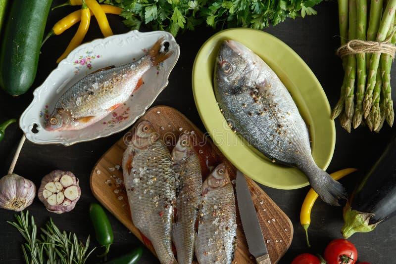 Взгляд сверху набора свежих, сырых рыб в различных блюдах и с овощами на черной таблице стоковая фотография