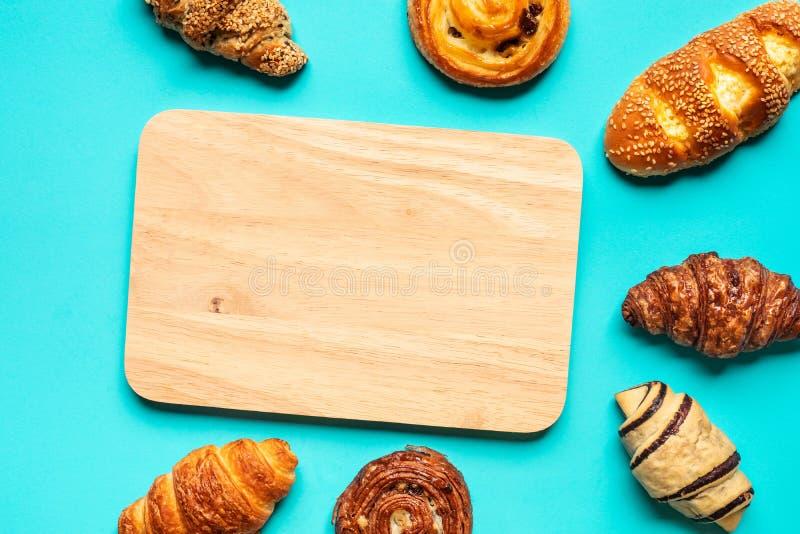 Взгляд сверху набора хлеба и пекарни с прерывая доской на голубой предпосылке цвета Еда и здоровые концепции стоковое изображение rf