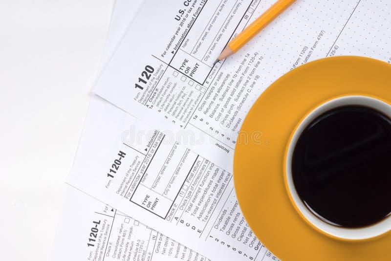 взгляд сверху 1120 налоговых форм с кофейной чашкой стоковая фотография