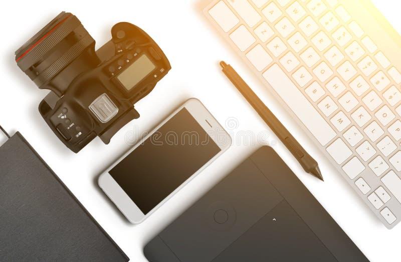 Взгляд сверху настольного компьютера состоять из фотографа камеры, клавиатура, умный телефон на белой предпосылке стола бесплатная иллюстрация