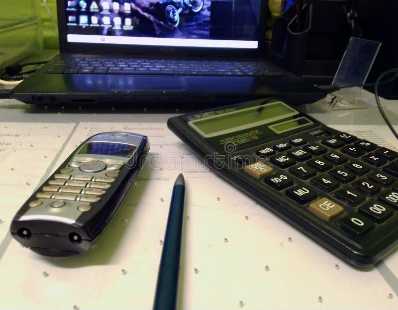 Взгляд сверху настольного телефонного аппарата, калькулятор, ручка, на запачканной предпосылке ноутбука, на рабочем столе стоковые фотографии rf