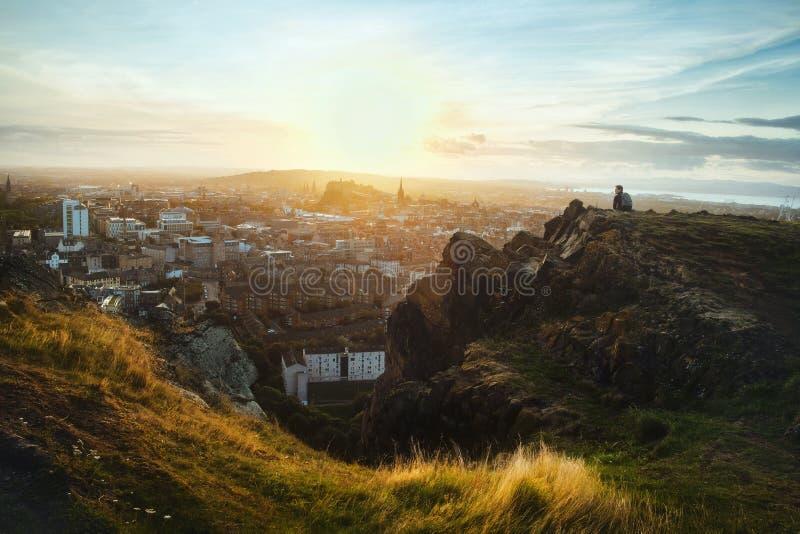 Взгляд сверху на городе Эдинбурга и сидя человека стоковая фотография