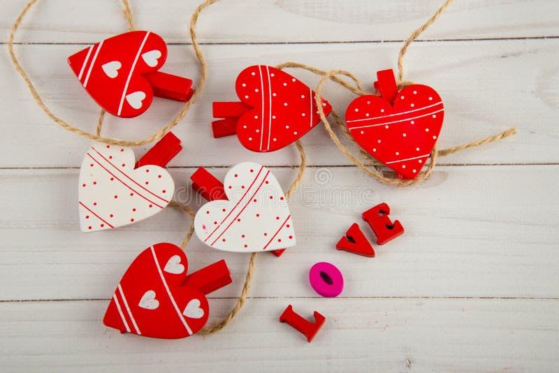 Взгляд сверху на красных сердцах кладя около слова ЛЮБОВ написанной деревянными письмами на белой предпосылке стоковое фото rf