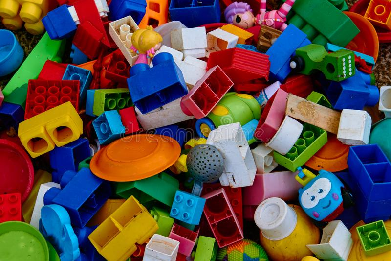 Взгляд сверху на пестротканых кирпичах игрушки и другие используемые игрушки который заполняют все изображение Улучшите для предп стоковое фото