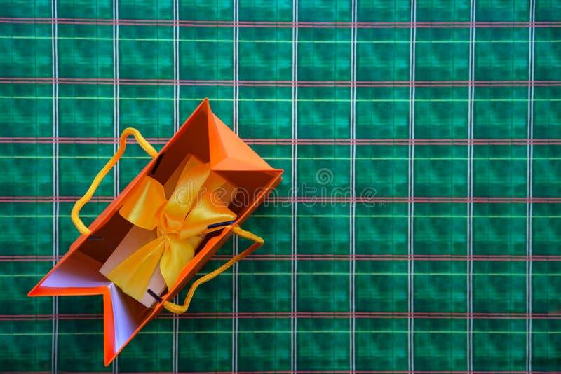 Взгляд сверху на подарочной коробке с желтой лентой смычка и хозяйственной сумке апельсина на яркой ой-зелен оранжевой шотландско стоковое фото rf