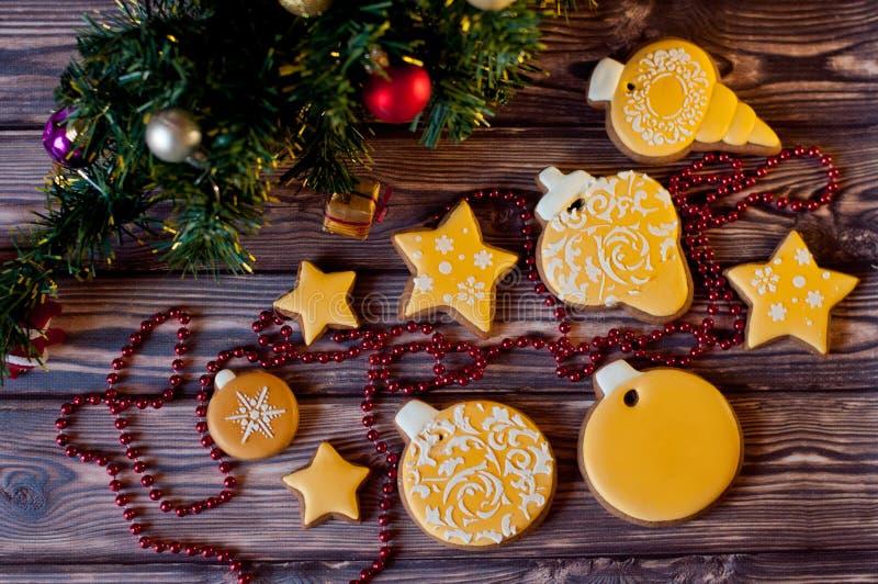 Взгляд сверху на разнообразии желтого цвета застеклило печенья ginferbread кладя около украшений рождества на деревянную предпосы стоковые фото