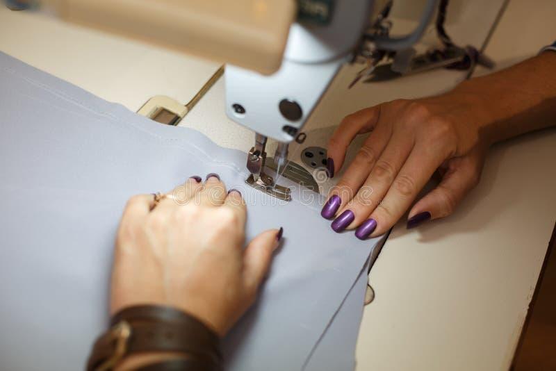 Взгляд сверху на руках женского портноя работая на швейной машине обрабатывающая промышленность платья стоковое фото rf