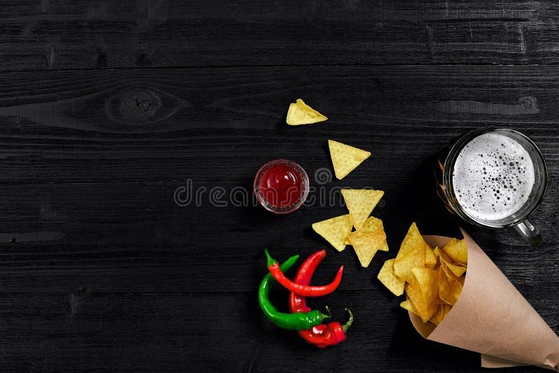 Взгляд сверху обломоков tortilla с соусом, стекло перца пива и красного chili на черной деревянной предпосылке стоковая фотография