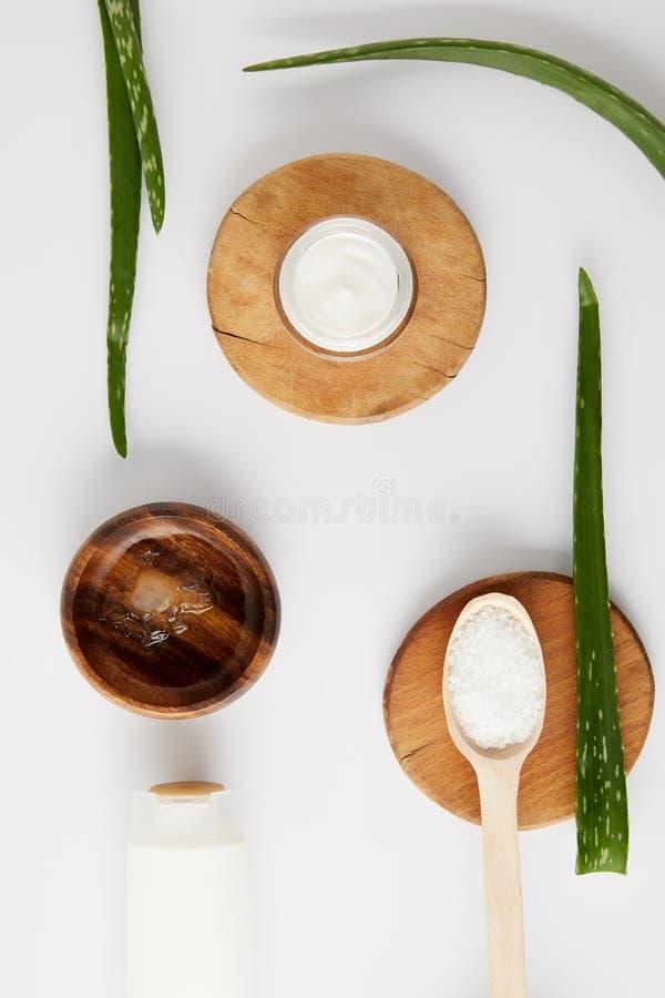 взгляд сверху органической сливк в контейнере и ложке с солью на деревянных кусках, листьев vera алоэ и деревянного шара с соком  стоковые изображения rf