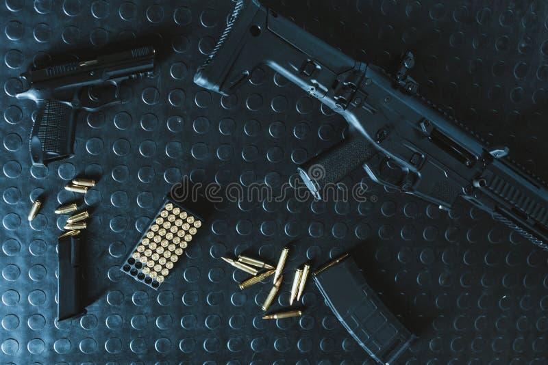взгляд сверху оружия и винтовки с пулями на таблице стоковые изображения