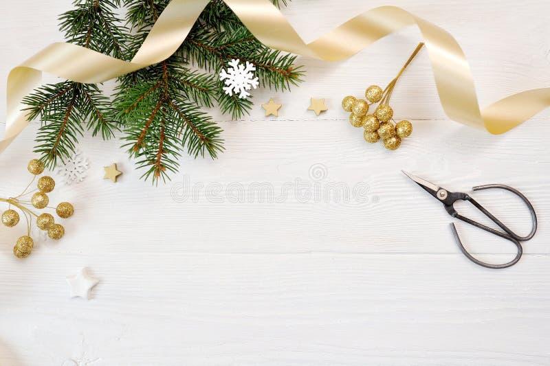 Взгляд сверху оформления рождества модель-макета и лента золота, flatlay на белой деревянной предпосылке, с местом для вашего тек стоковые фото