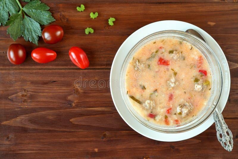 Взгляд сверху очень вкусного домодельного супа фрикаделек с томатами, красным перцем, сельдереем и рисом на деревянном столе Трад стоковые фотографии rf