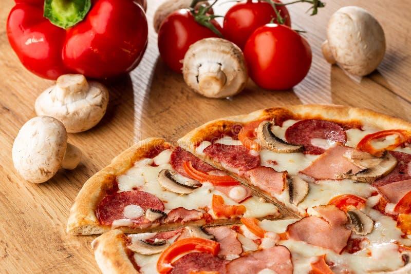 Взгляд сверху очень вкусной пиццы Capricciosa на деревянном столе Ингредиенты слезли томат, сыр, ветчину, грибы, салями стоковая фотография rf