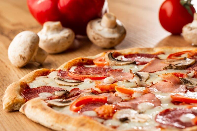 Взгляд сверху очень вкусной пиццы Capricciosa на деревянном столе Ингредиенты слезли томат, сыр, ветчину, грибы, салями стоковые изображения