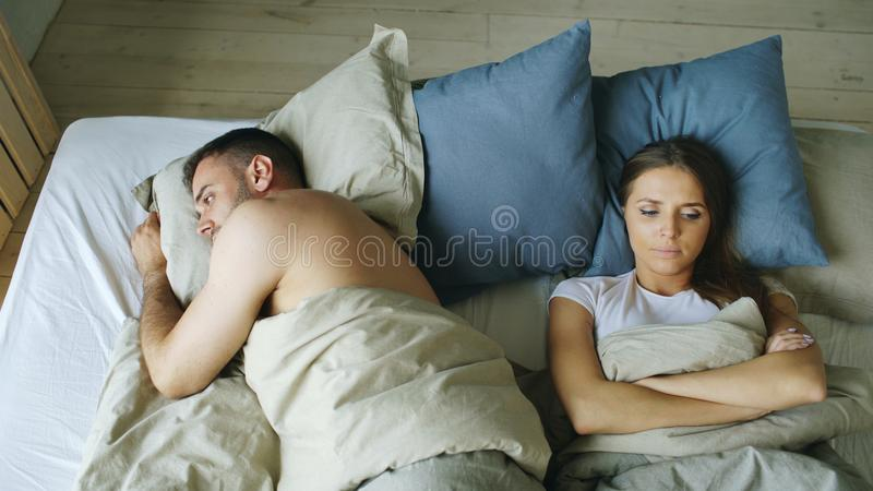 Взгляд сверху пар осадки лежа бессонных в кровати обиденной из-за ссоры стоковые изображения rf