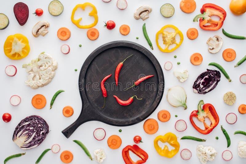 взгляд сверху перцев красного chili на круглой деревянной доске и свежих отрезанных овощах стоковое изображение